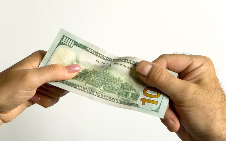 two hands pulling on $100 bill