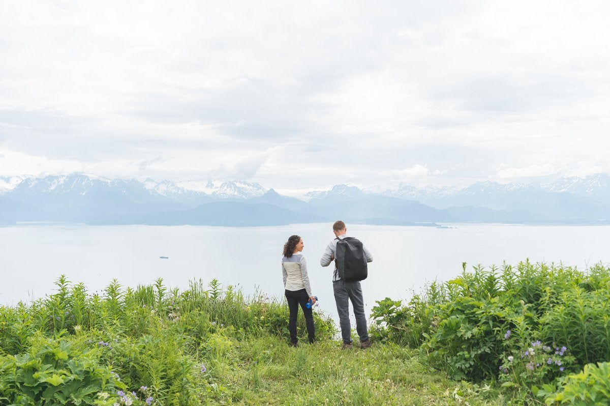 Two hikers at a grassy lookout point with water and mountains in the distance.
