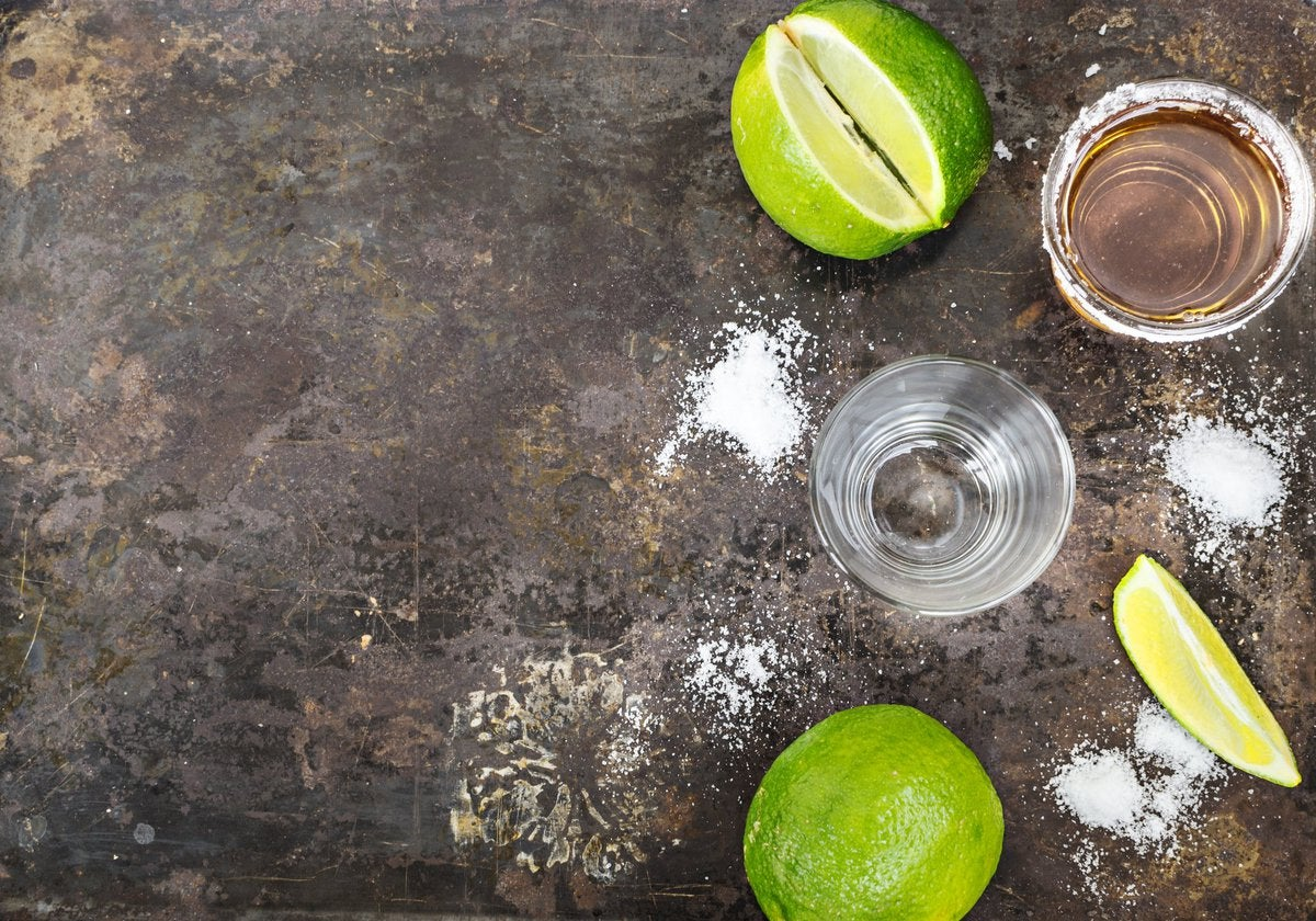 two limes, two shot glasses, tequila, and salt on a table.