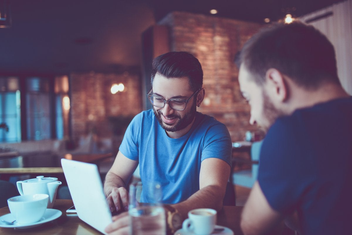 Two men looking at a laptop together in a cafe.