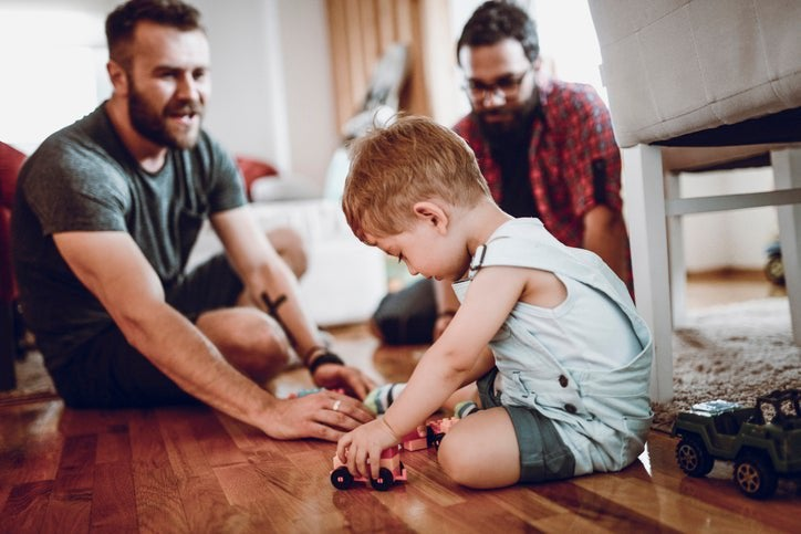 Two fathers playing with toy cars on the floor with their toddler son.