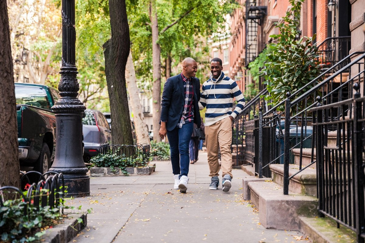 Two men laughing while walking down a residential city street.