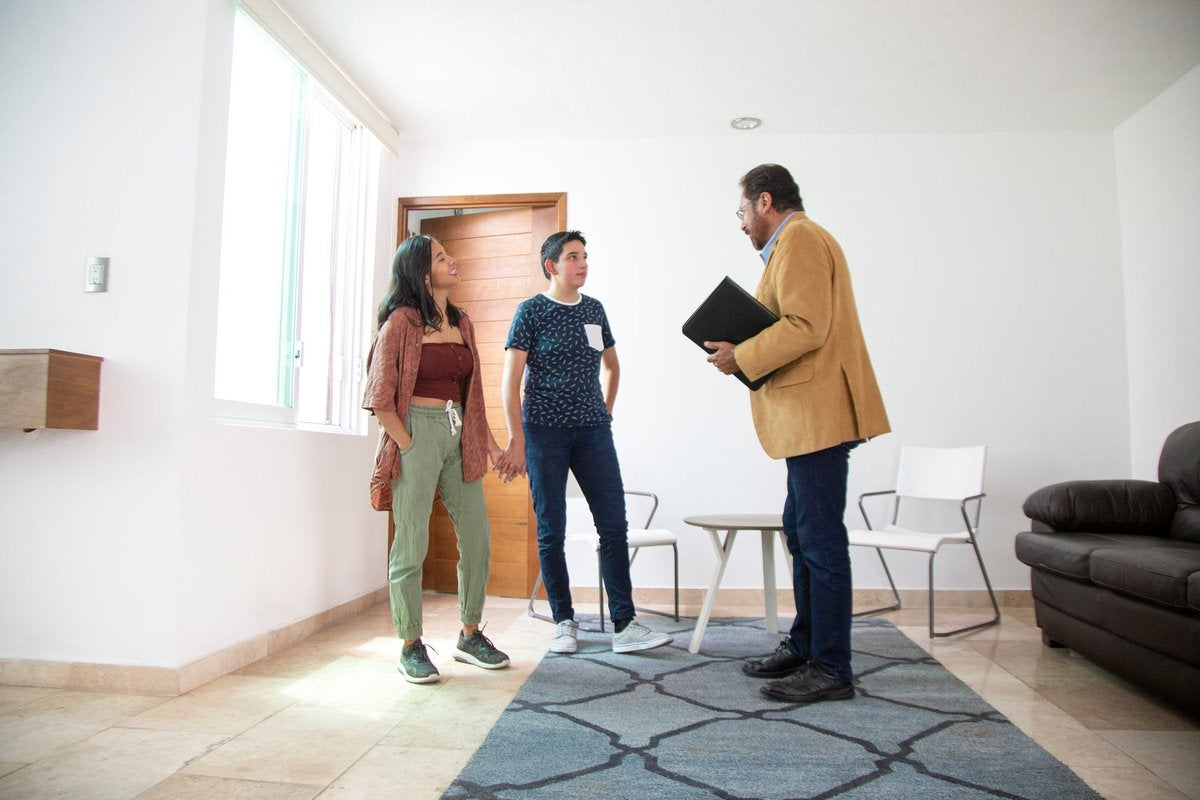 Two people holding hands while standing in the living room of a new house and talking with a realtor.