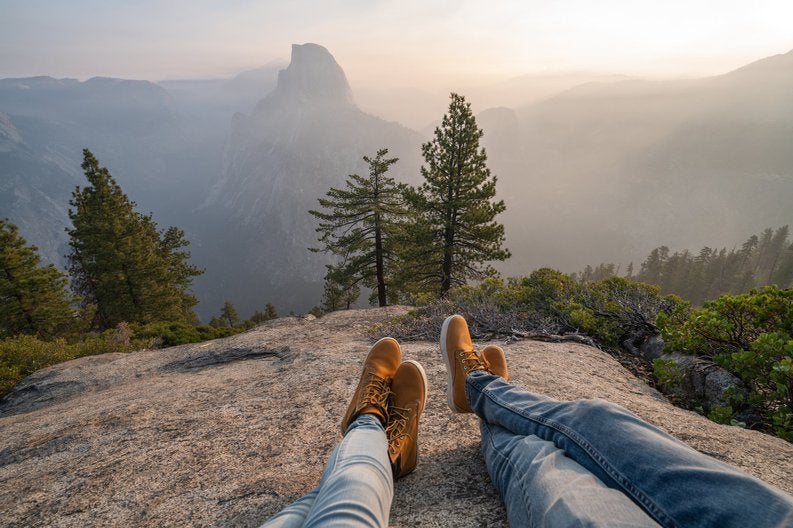 Two people lying on a rock in overlooking trees and Half Dome in Yosemite.