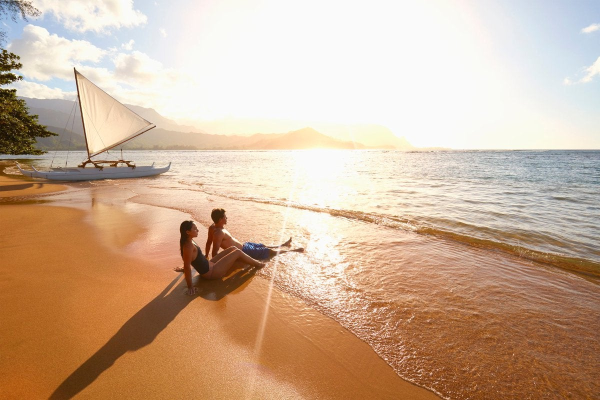 Two people sitting in the waves on a tropical beach at sunset with a sailboat behind them.