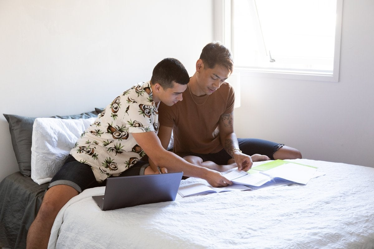 Two people sitting on a bed and looking at paperwork next to an open laptop.