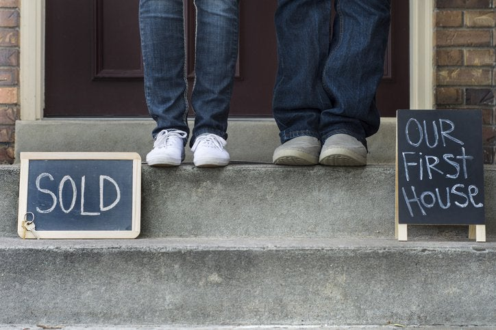 Two sets of feet standing on the front steps of a home next to signs saying Sold and Our First House.