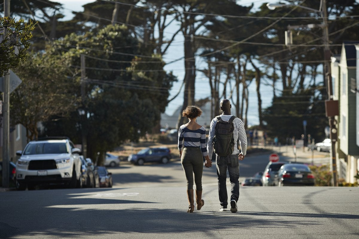 Two people holding hands while walking down the middle of a street surrounded by trees and parked cars.