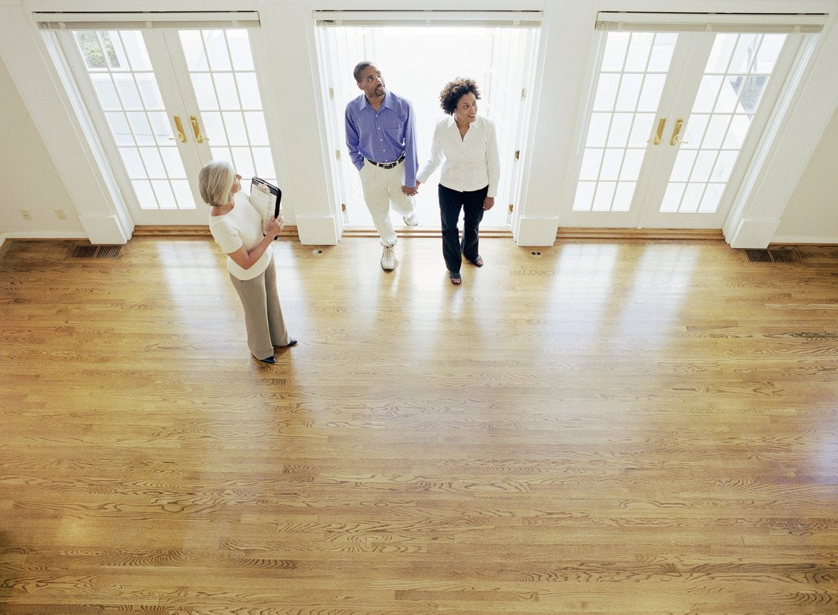 Two people walking into an empty house with their realtor.