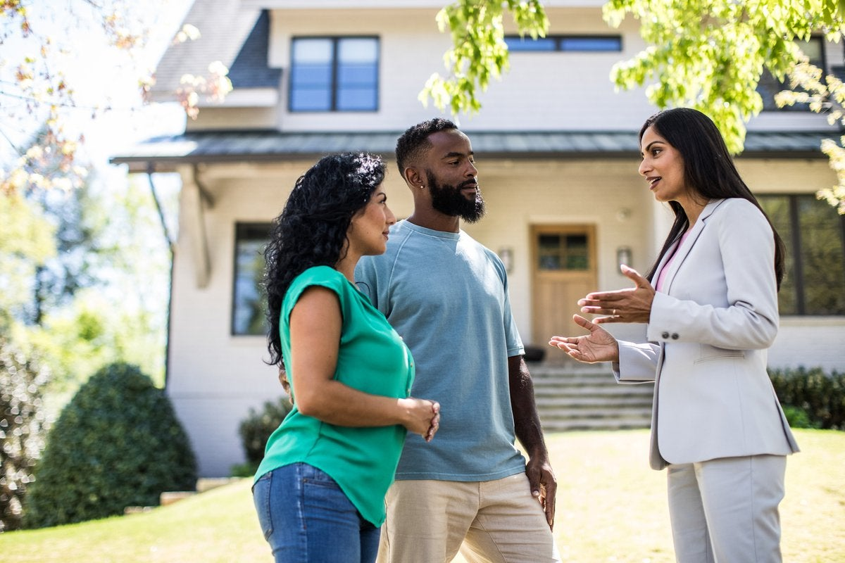 Two people standing in the front yard of a house and speaking with their realtor.
