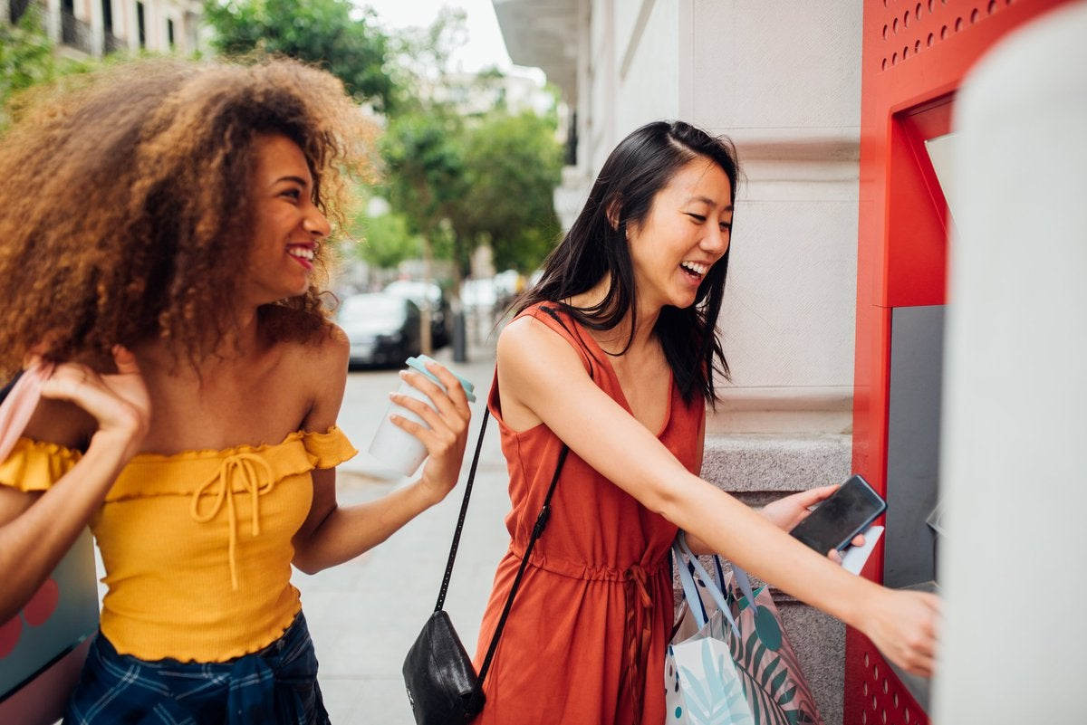 A young woman using an ATM on the street while her friend waits for her.