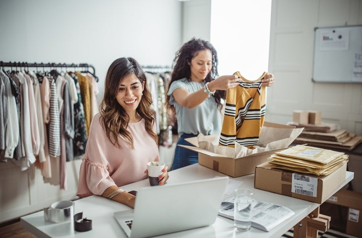 One woman packing clothes into shipping boxes while the other checks her laptop at a table in a clothing store storeroom.