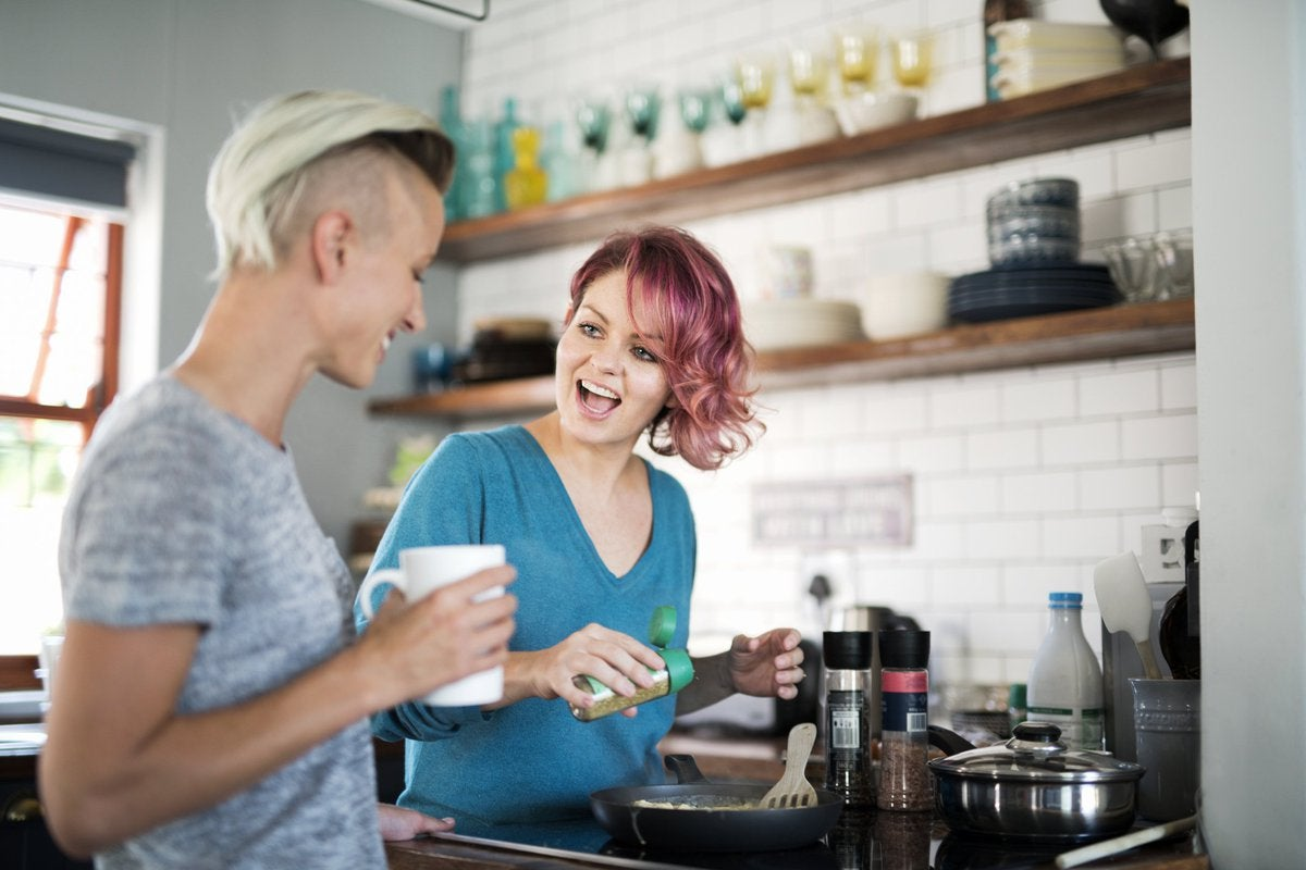 A woman cooking at the stove and laughing with her girlfriend drinking coffee.
