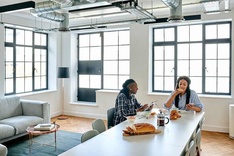 Two women eating breakfast together in their bright loft apartment.