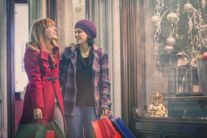 Two smiling women dressed in warm clothes window shopping for holiday gifts.