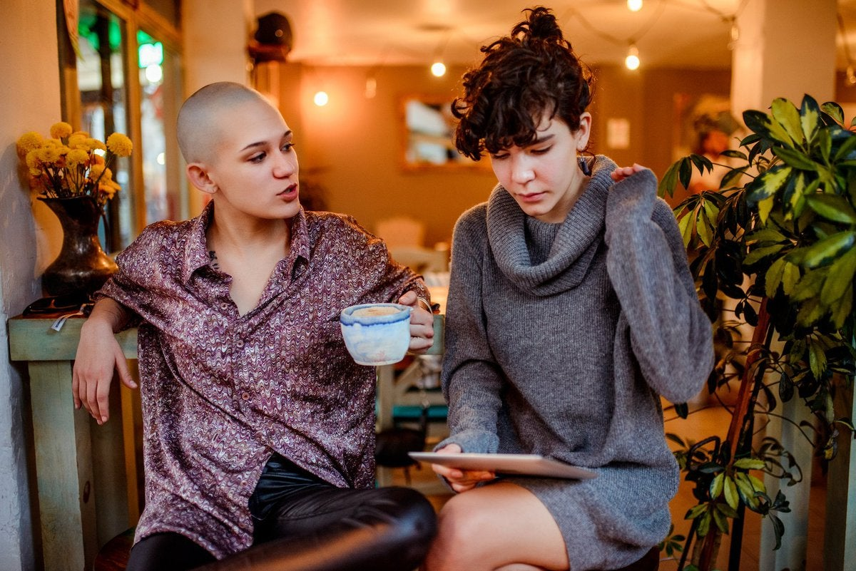 Two women sitting in a cafe while one looks at a tablet in her lap.