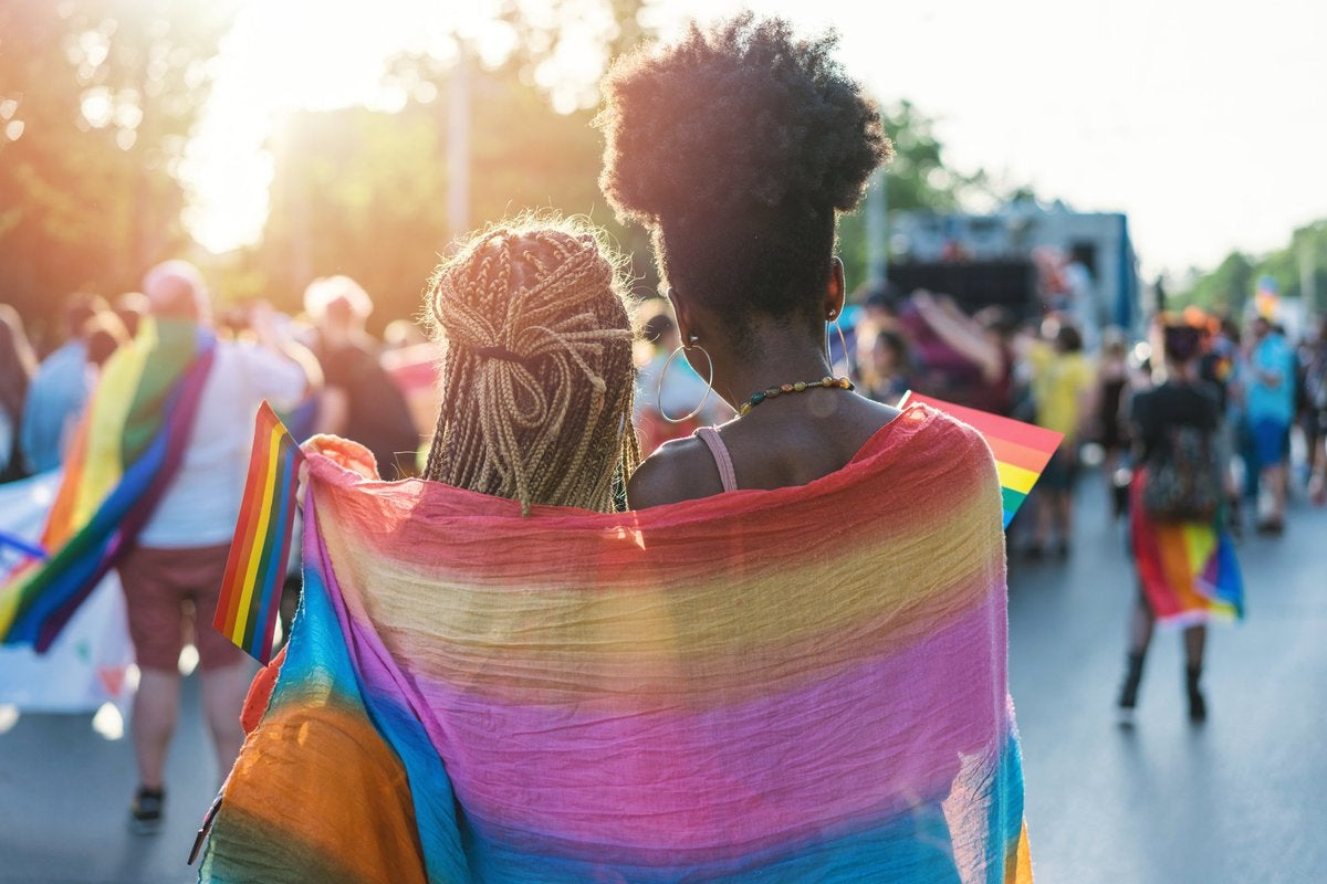 Two women wearing a rainbow flag around their shoulders at a Pride parade.