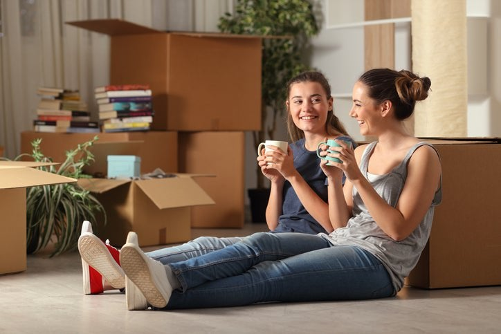 Two women sitting on the floor next to moving boxes while drinking coffee.