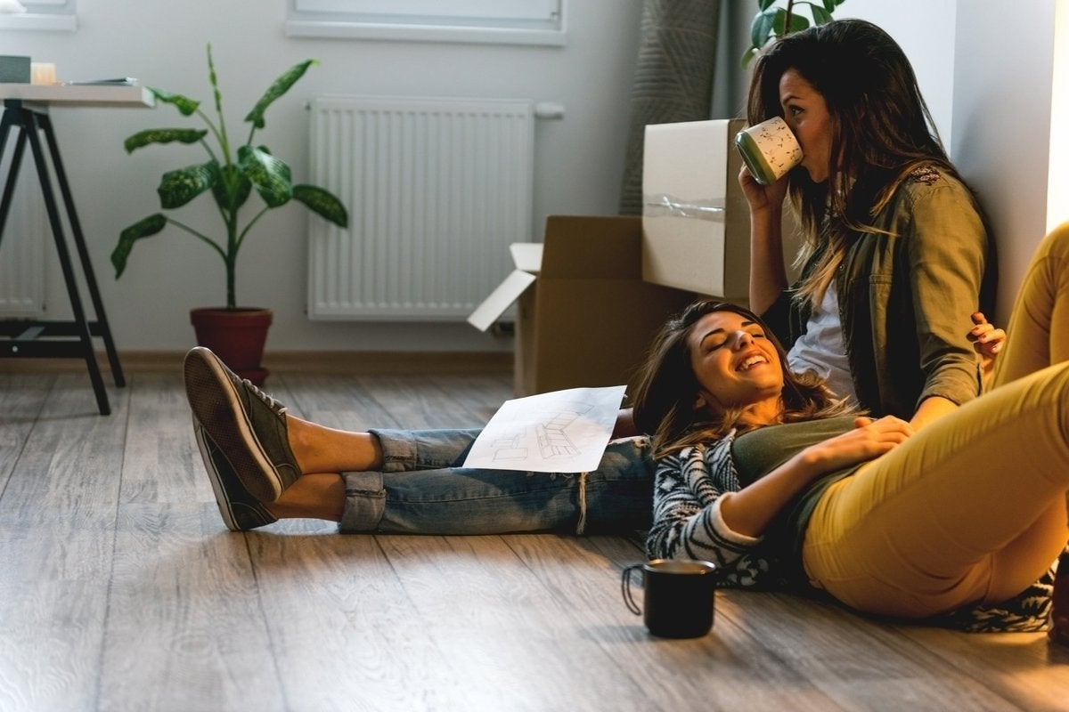 A woman lying on the floor with her head resting on her girlfriend's lap.