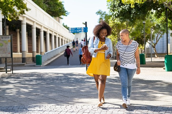 Two young women walking down the street and smiling while one holds her cell phone.