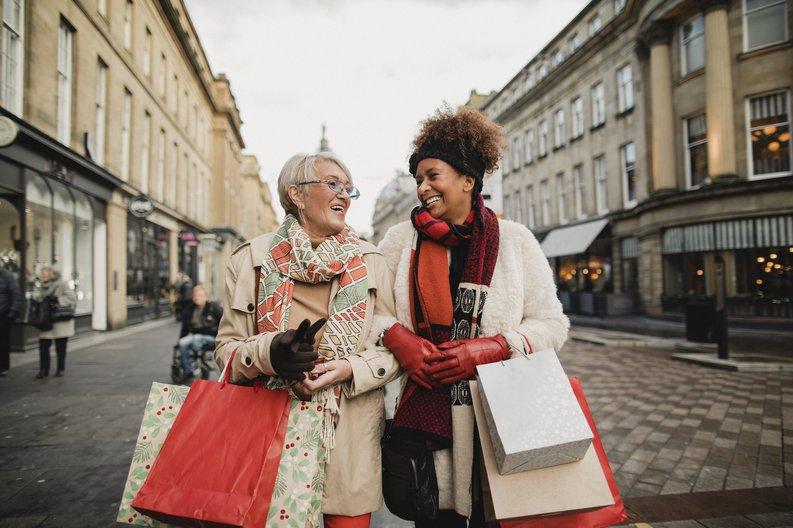 Two women walking down a street arm in arm carrying shopping bags.