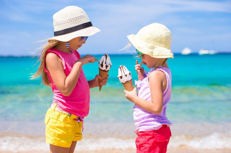 Two young girls holding ice cream cones on the beach