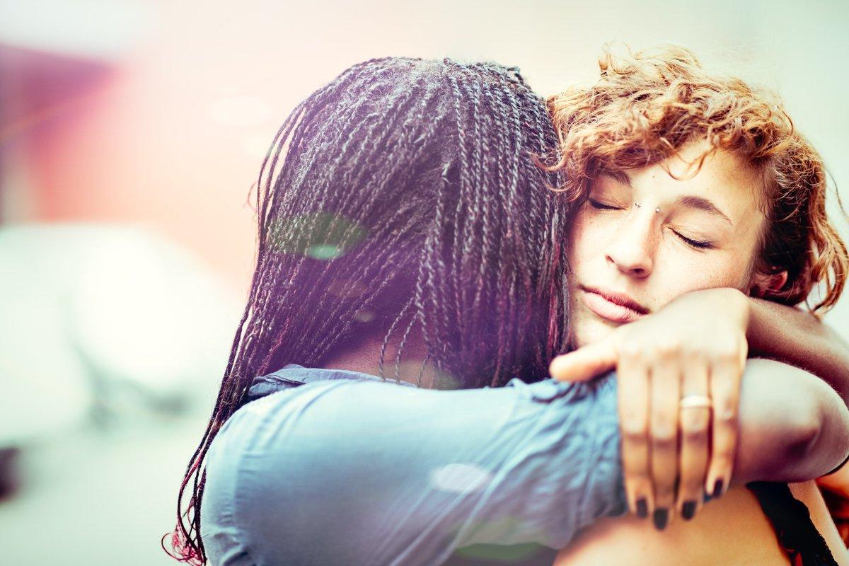 A young woman hugging her girlfriend.