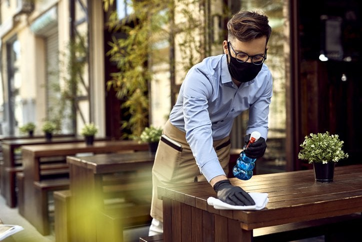 A male waiter cleaning wooden outdoor tables with disinfectant spray and a towel.