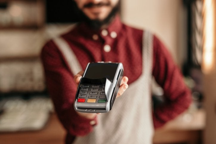 A waiter wearing an apron and holding up a credit card reader awaiting payment.