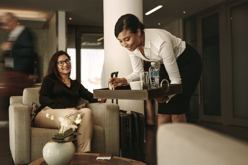 A waitress bringing a tray of drinks to a customer in an airport lounge.