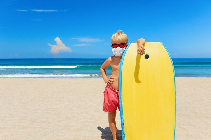 A boy in a mask on a beach poses with his wake board.