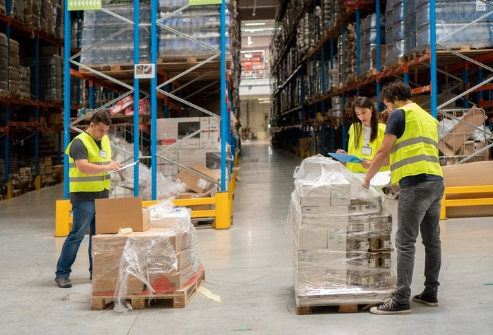 One woman and two men wearing safety vests while unpacking a pallet of boxes in a warehouse.