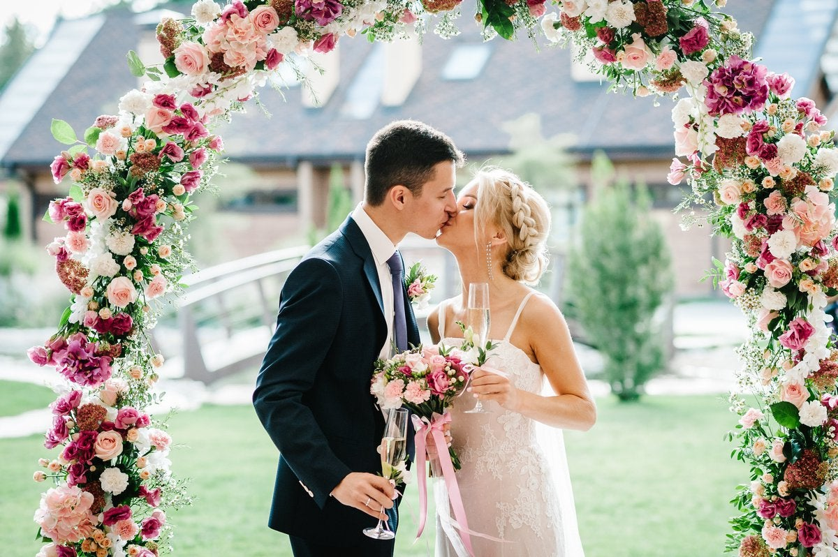 A bride and groom kissing underneath a flower arch.