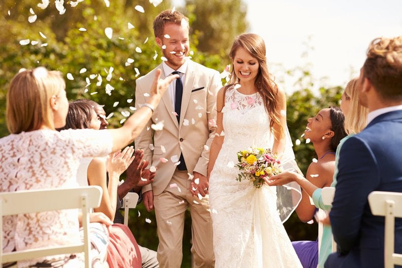 wedding guests throw flowers at newlywed couple