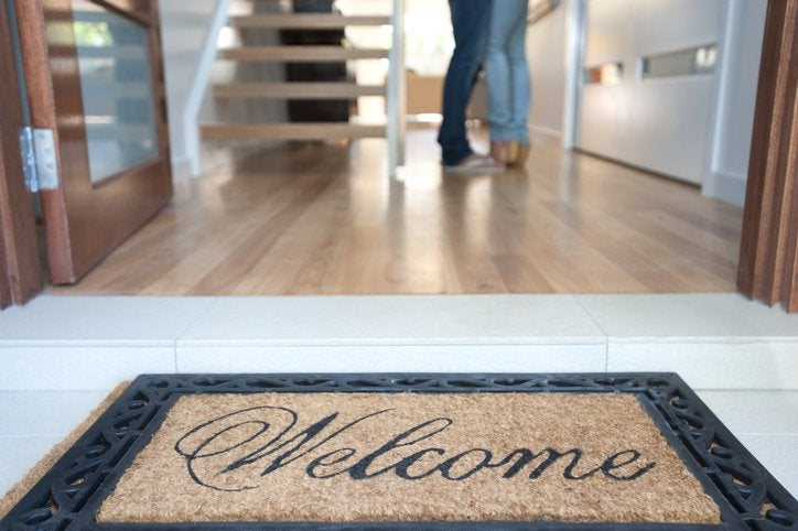 A welcome mat at the open front door of a new house with a man and woman standing inside.
