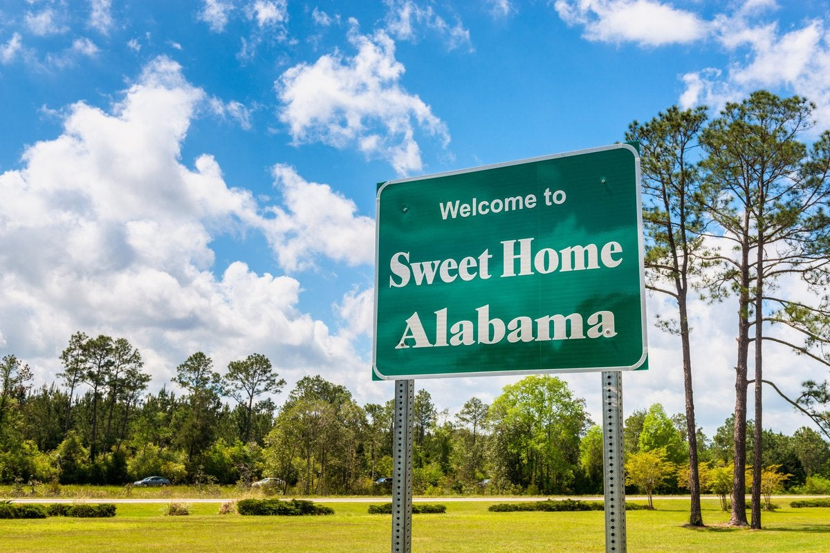 Green grass and a blue sky behind a road sign that says Welcome to Sweet Home Alabama.