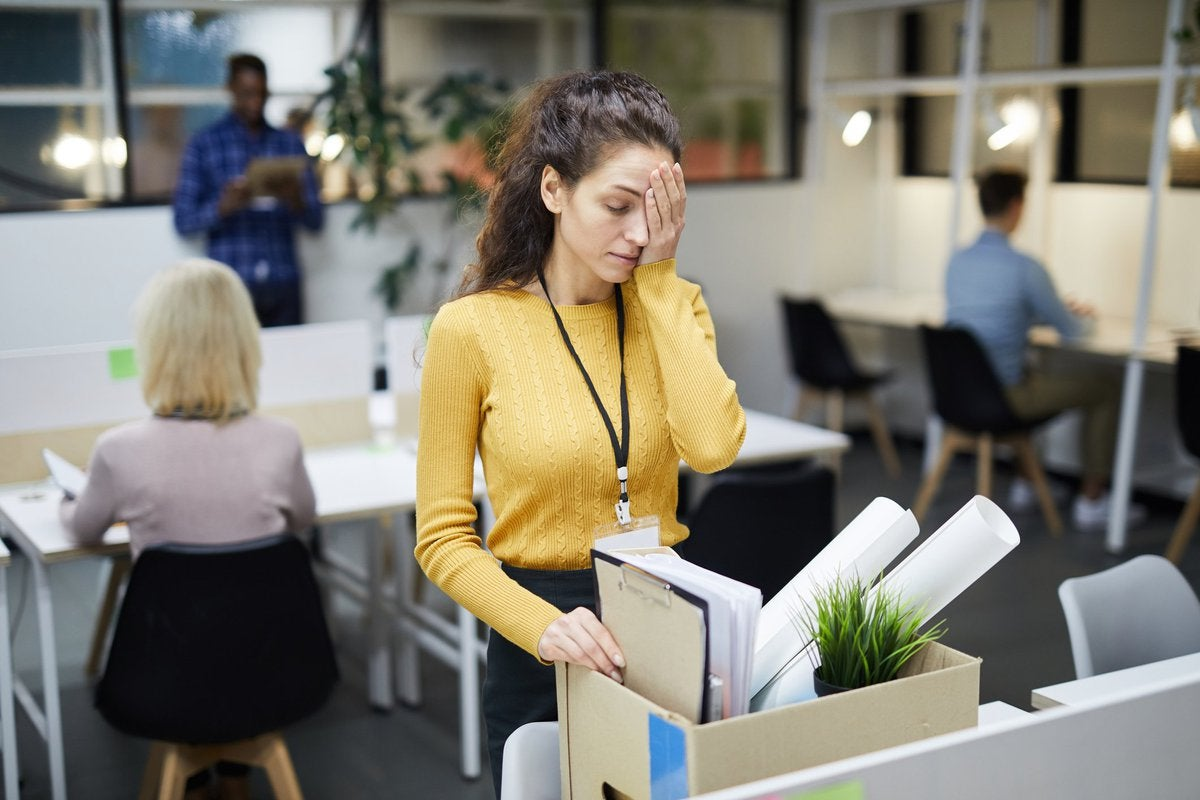 Sad-looking woman packing up her desk at an office