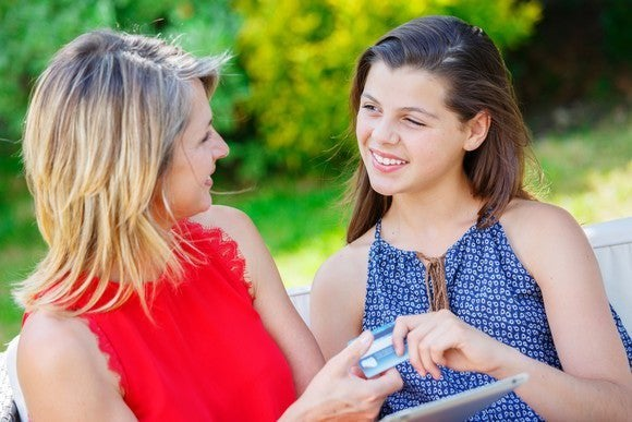 Woman handing teenage girl a credit card