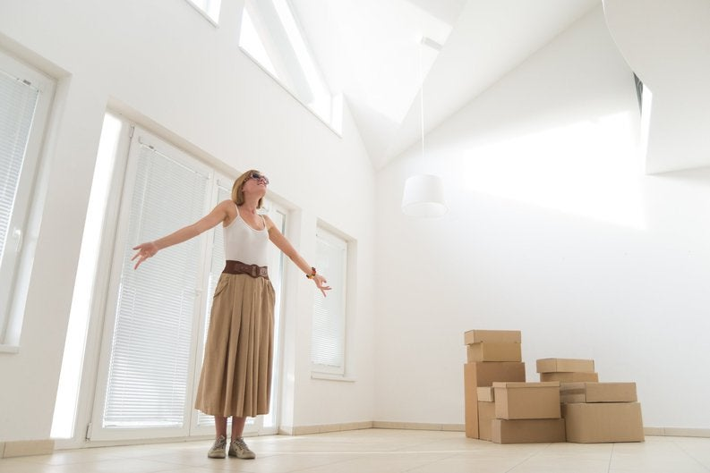 A woman celebrating with her arms out while standing next to moving boxes in her new home.