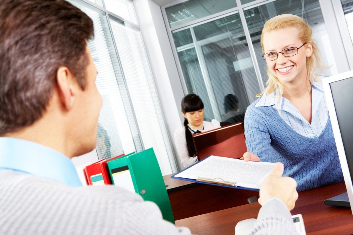 Smiling woman handing financial papers to banker.