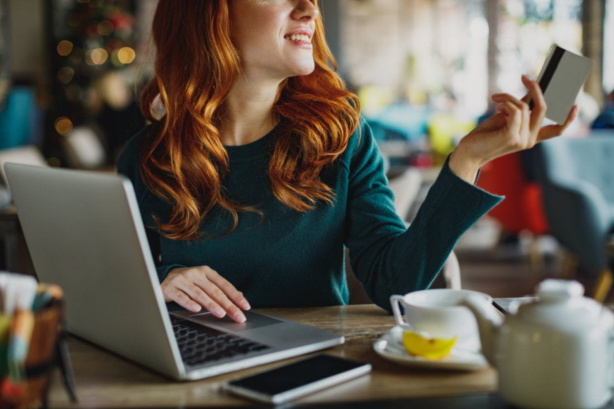 A woman sitting at a cafe table with tea and a laptop and holding out her credit card.