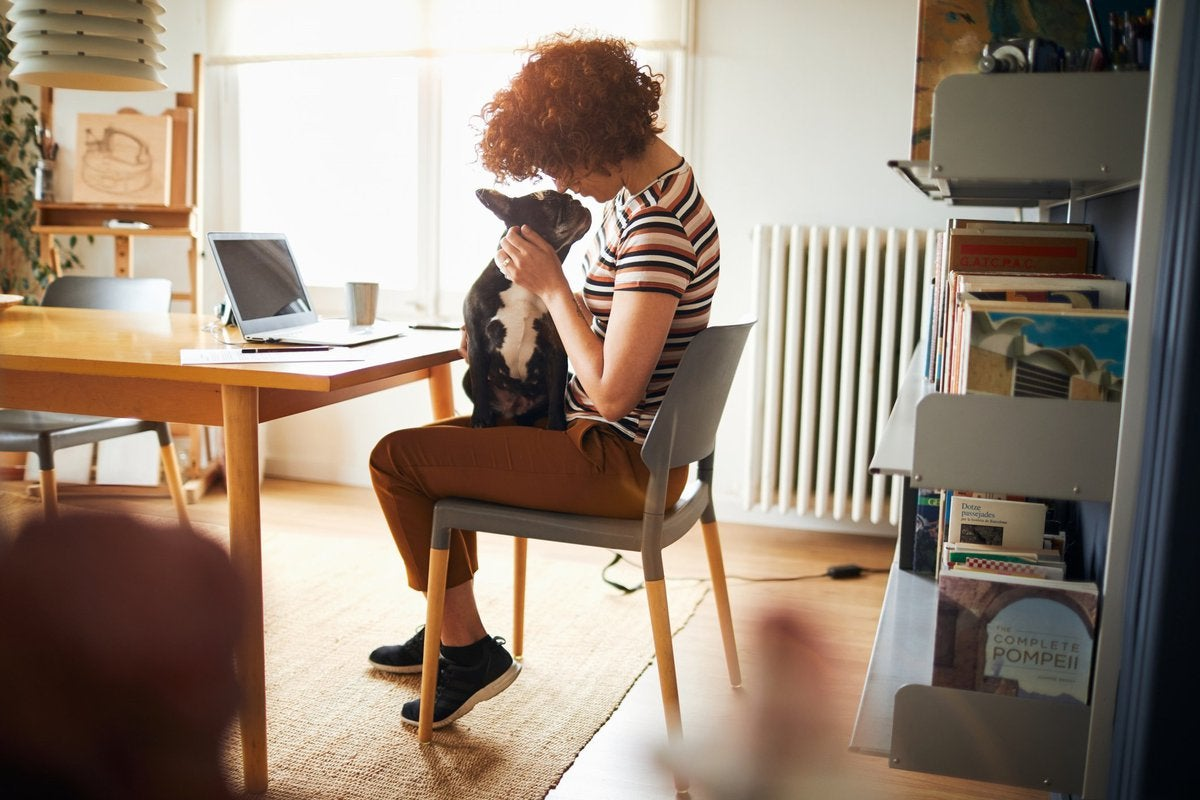 A woman sitting in her home office snuggling with a dog on her lap.