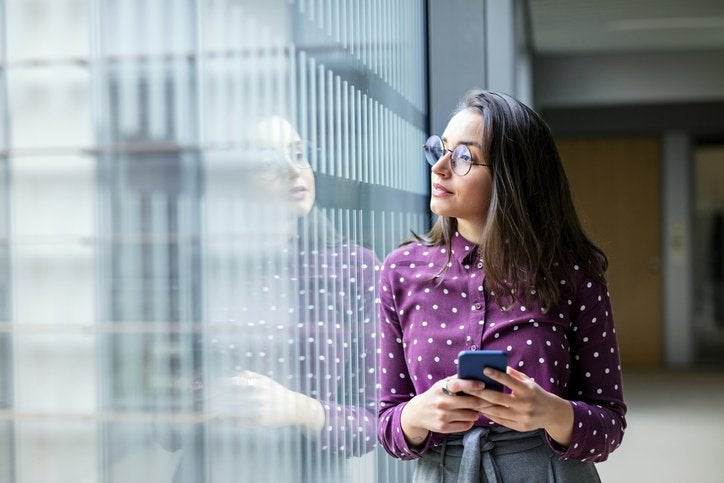 A young professional woman looking thoughtfully out an office window while holding a phone.