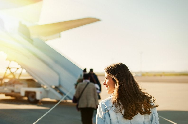A woman standing on the sunny tarmac and waiting to board a plane.