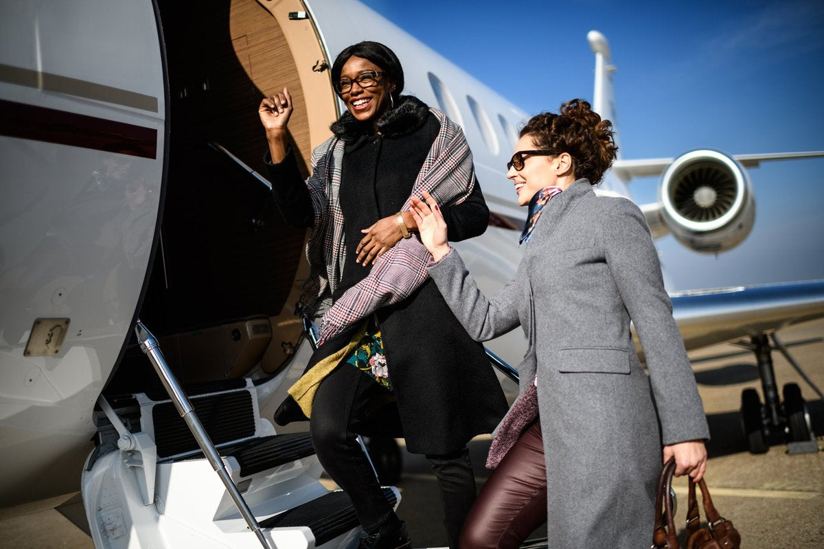 Two women boarding a private jet.