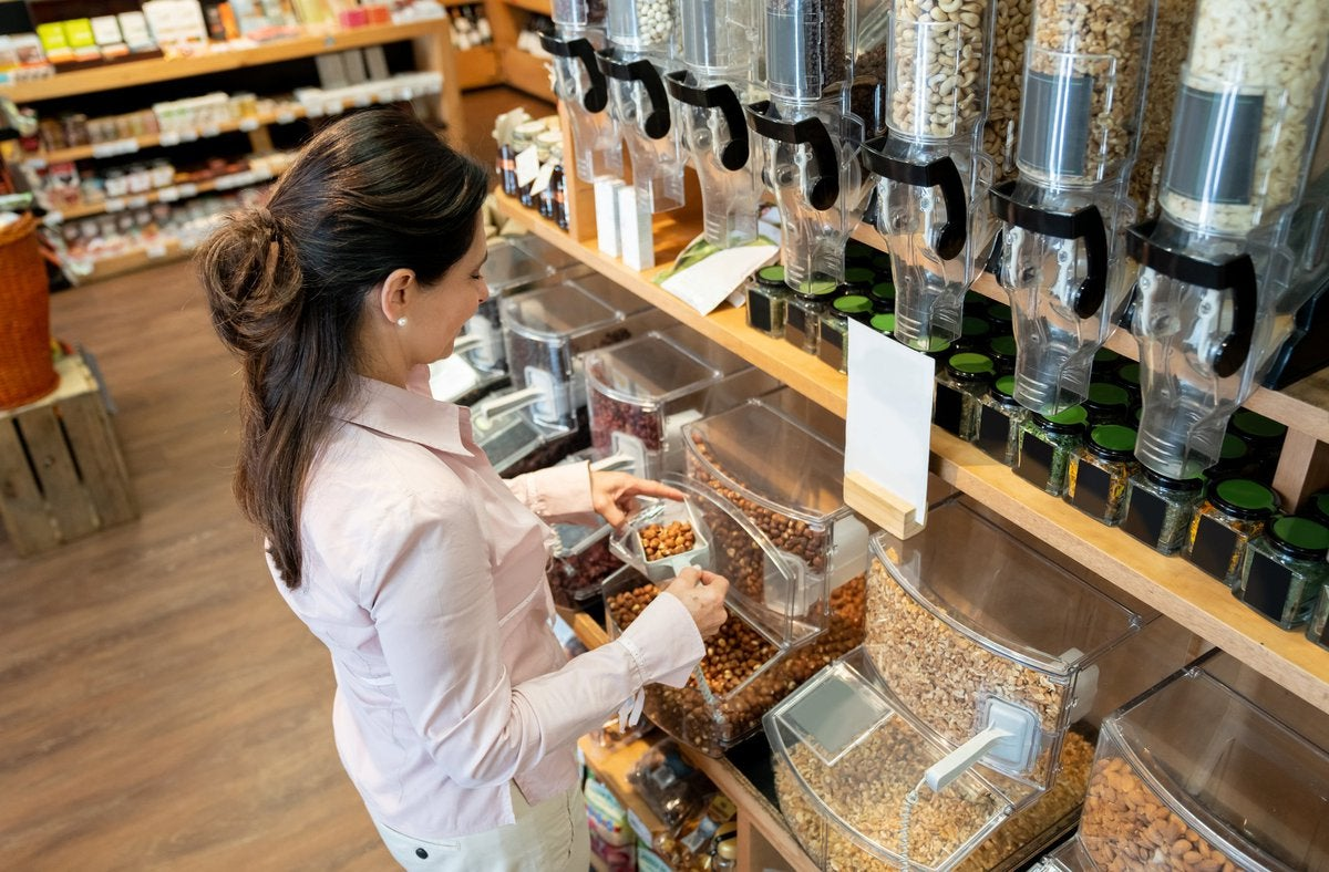 A woman bulk shopping for dry goods at a grocery store.