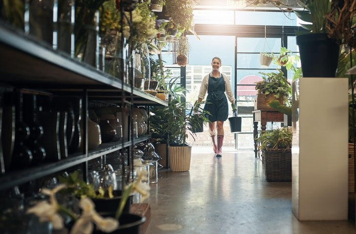 A woman wearing an apron and carrying watering cans into her small business filled with shelves of plants.