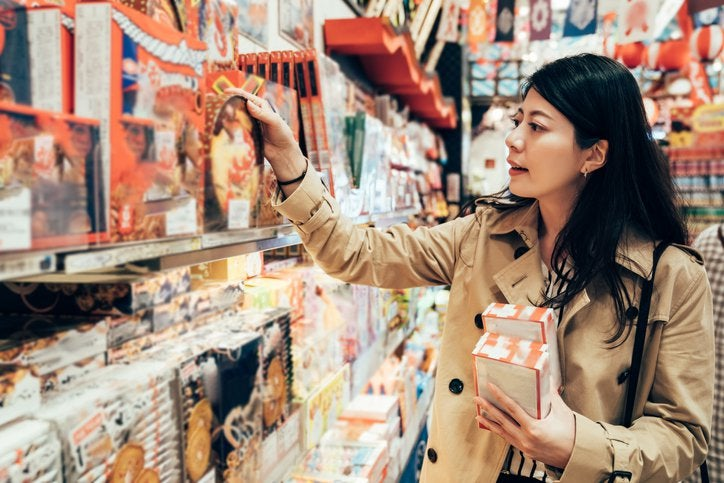 A woman browsing the shelves of a store and picking out boxes of holiday sweets.