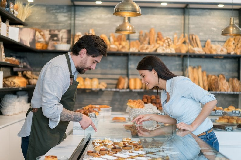 A male cashier helping a woman pick out a pastry at a bakery.