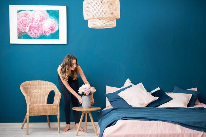 A woman arranging flowers on a bedside table in a well-decorated bedroom.